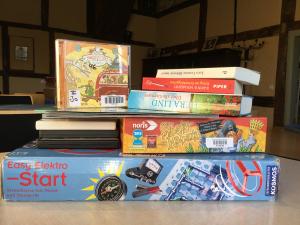 Das Bild zeigt einen kleinen Stapel mit ausleihbaren Medien. Z.B. Bücher, CDs und PC-Spiele